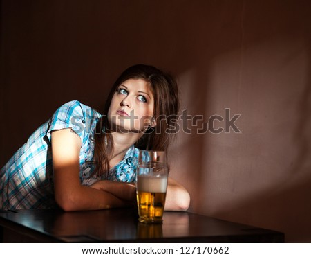cute young woman drinking lager sitting in bar
