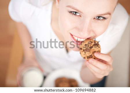 Cute young woman eating cookies and drinking milk, horizontal picture from above, model is smiling into the camera