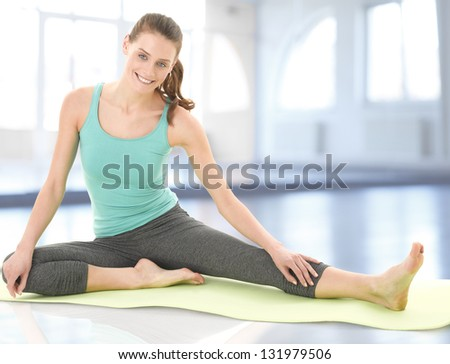 Cute young woman exercising and stretching in the fitness club - stock photo