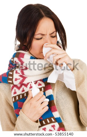 Cute young woman having caught cold, with nose spray and handkerchief in her hands