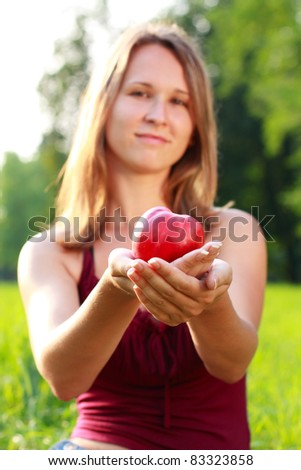 Cute young woman holding an apple in her hands against the background of nature