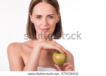 Cute young woman holding green apple