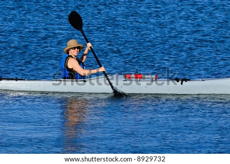 Cute young woman in straw hat is kayaking in idyllic blue waters of Mission Bay, San Diego, California - stock photo