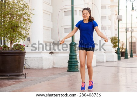 Cute young woman jumping a rope as part of her workout in the city - stock photo