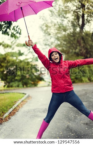 Cute young woman jumping with umbrella - stock photo