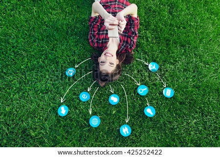 Cute young woman laying on the grass, using a cell phone with various icons  - stock photo