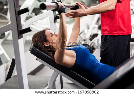 Cute young woman lifting a barbell with the help of a personal trainer in a gym - stock photo