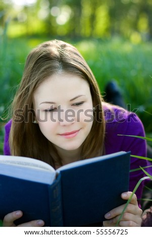 Cute young woman lying on the grass and reading a book - stock photo