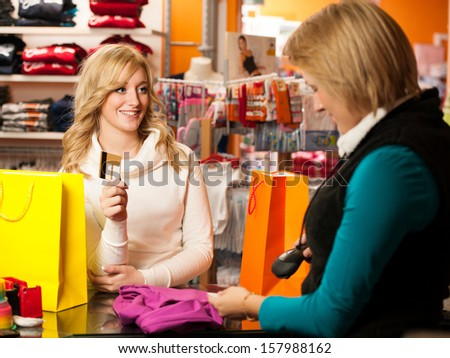 Cute young woman paying after successful purchase with credit card - girl on shopping in clothes shop - stock photo