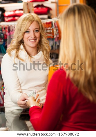 Cute young woman paying after successful purchase with credit card - girl shopping in a clothes shop - stock photo