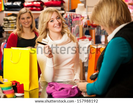 Cute young woman paying after successful purchase with credit card - girls on shopping