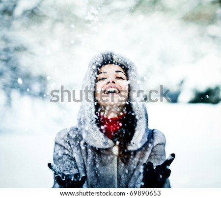 Cute young woman playing with snow in fur coat outdoors - stock photo
