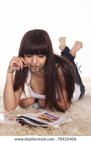 cute young woman reading on a carpet