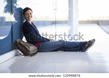 Cute young woman relaxing in the hallway at school - stock photo