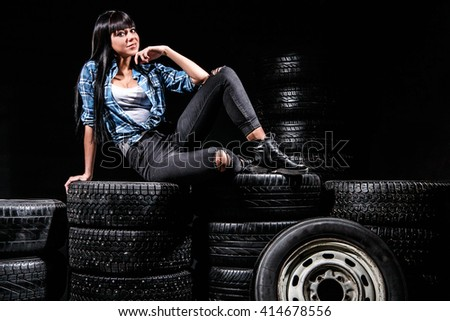 Cute young woman sitting on a tires over black background - stock photo