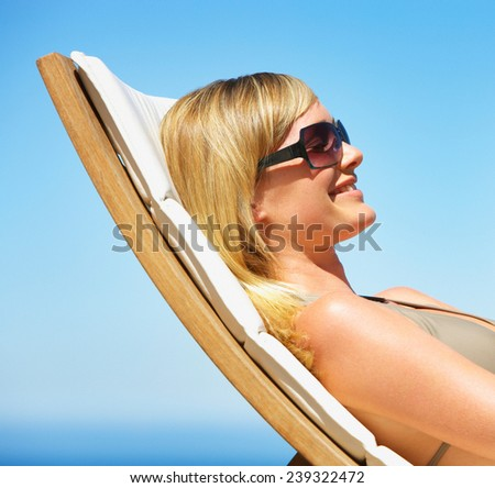 Cute young woman sitting on sunbed and smiling - stock photo