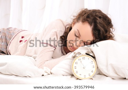 cute young woman sleeping on bed with white bedding and alarm clock