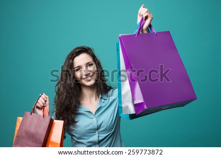 Cute young woman smiling and holding a lot of shopping bags - stock photo