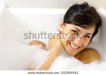 Cute young woman smiling in bath tub full of foam - stock photo
