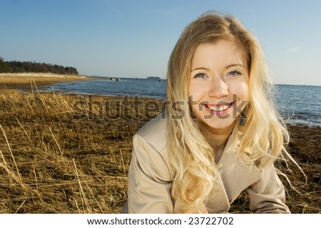 Cute young woman smiling on the beach in winter - stock photo