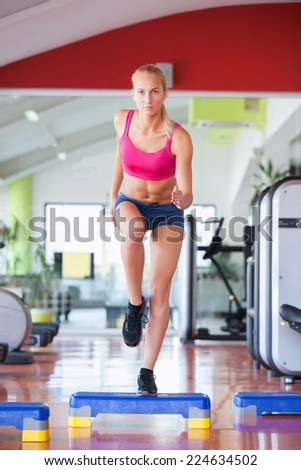 Cute young woman stretching and warming up before working out at a gym - stock photo