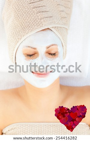Cute young woman with closed eyes having white cream on her face against heart - stock photo