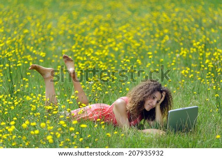 Cute young woman with curly hair lying reading a book in a wildflower meadow full of colorful yellow summer flowers as she relaxes in the tranquility and beauty of nature - stock photo