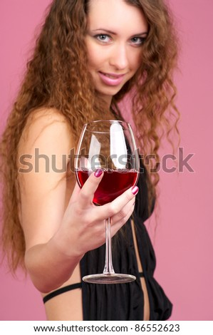 Cute young woman with glass of red wine, selective focus