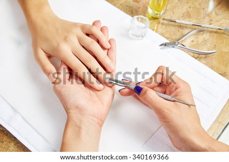 Cuticle pusher tool in nails salon woman hands treatment - stock photo