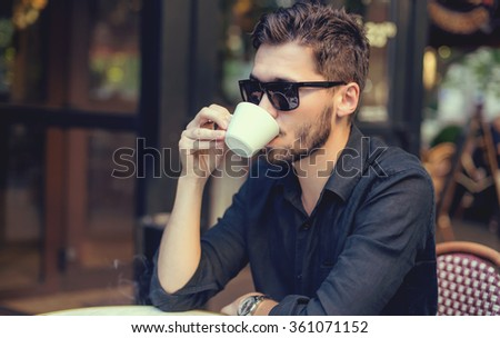 Cutie man with cup of coffee looking at mobile phone outdoors - stock photo