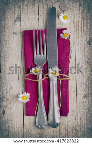 Cutlery - fork and knife on purple napkin on old wooden table with some daisies in vintage stile - stock photo