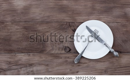 cutlery, knife, fork, plate on a wooden table