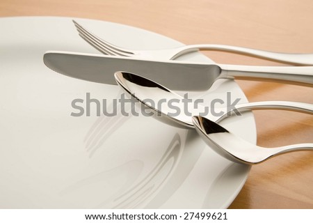 Cutlery on a white plate on a wooden table