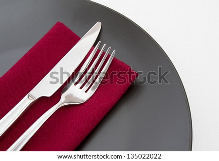 Cutlery on red napkin with black plate - stock photo
