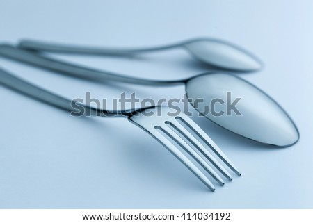 Cutlery set on light background, Silverware set of fork, spoons and knife. Toned image, shallow DOF - stock photo