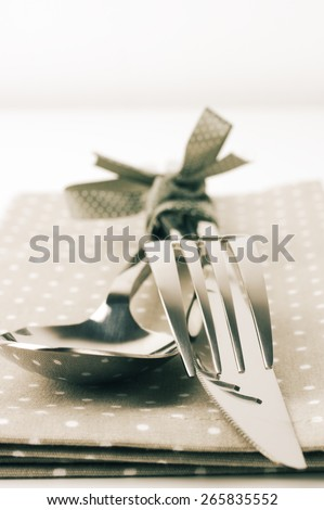 Cutlery set: spoon, fork and knife on napkin close-up. Toned image. - stock photo