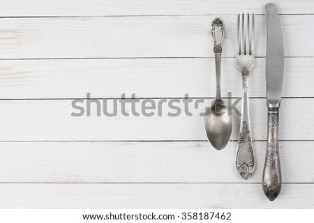 Cutlery set: vintage knife, fork and spoon on white wooden background.