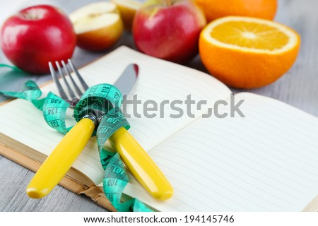Cutlery tied with measuring tape and book with fruits on wooden background - stock photo