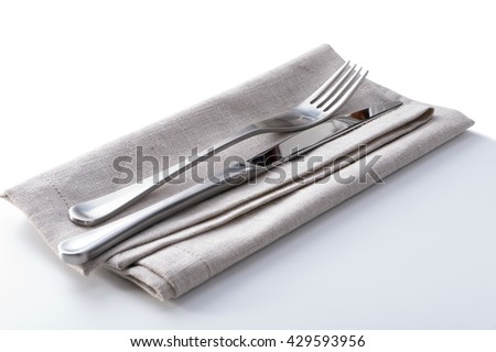 cutlery with linen napkin on white background  - stock photo