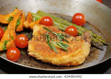Cutlet with potato wedges, tomatoes, green asparagus, garnished with parsley and rosemary - stock photo