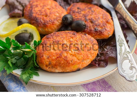 Cutlets of salmon on lettuce leaves with lemon and olives. Selective focus - stock photo