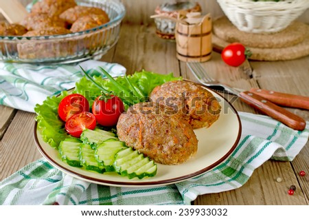 Cutlets with buckwheat and a side dish of vegetables. On the plate are lettuce, cucumbers and tomatoes.