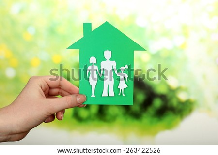 Cutout house with paper family in female hand on bright blurred background - stock photo