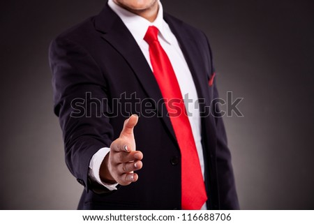 cutout of a business man offering a handshake, on dark background - stock photo