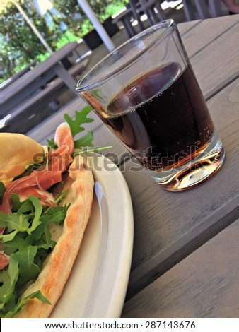 Cutout of a summer dish with a glass of chilled sparkling drink on a wooden table, and a summer outdoors scenery in background - stock photo