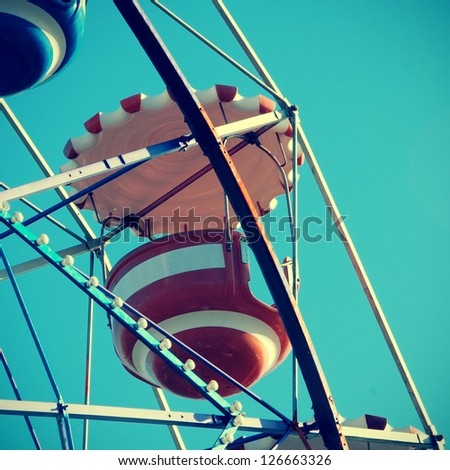 cutout of a vintage ferris wheel over the blue sky
