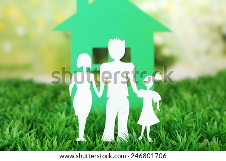 Cutout paper family and house on green grass and bright blurred background - stock photo