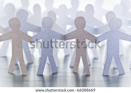 Cutouts of identical paper men - stock photo
