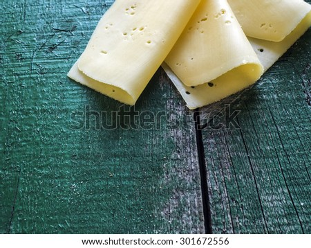 Cuts os cheese on the old weathering green table - stock photo