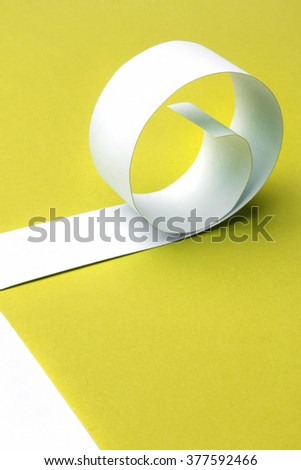 Cutted and rolled white paper with yellow background - stock photo